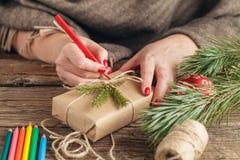 La Navidad vista de las manos que escriben en la caja de regalo packed Fotografía de archivo libre de regalías