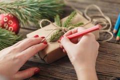 La Navidad vista de las manos que escriben en la caja de regalo packed Foto de archivo libre de regalías