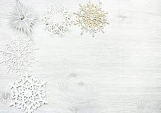 La Navidad y Año Nuevo La Navidad juega, los copos de nieve en un fondo blanco de madera Fotos de archivo libres de regalías