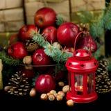 La Navidad y Año Nuevo Manzanas con los conos del pino y nueces en bas Imagen de archivo