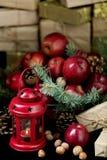 La Navidad y Año Nuevo Manzanas con los conos del pino y nueces en bas Fotos de archivo