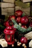 La Navidad y Año Nuevo Manzanas con los conos del pino y nueces en bas Foto de archivo libre de regalías