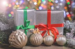 La Navidad y Año Nuevo, regalos con el fondo borroso de guirnaldas Imagen de archivo libre de regalías