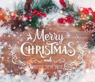 La Navidad y Año Nuevo tipográficos en fondo del día de fiesta con la decoración de Navidad, la rama del árbol de abeto y la niev Foto de archivo