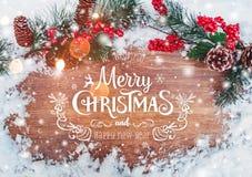 La Navidad y Año Nuevo tipográficos en fondo del día de fiesta con la decoración de Navidad, la rama del árbol de abeto y la niev Foto de archivo libre de regalías