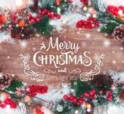 La Navidad y Año Nuevo tipográficos en fondo del día de fiesta con la decoración de Navidad, la rama del árbol de abeto y la niev Imagen de archivo