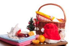 La Navidad y accesorios de la playa con la cesta sobre blanco Fotos de archivo