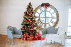 La Navidad y el Año Nuevo adornaron el sitio interior blanco con los presentes y el árbol del Año Nuevo con la bola roja de la de Fotos de archivo libres de regalías