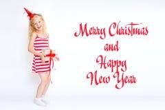 La Navidad y el Año Nuevo cardan 2019 con la pequeña muchacha rubia linda feliz en vestido rojo y blanco del traje del carnaval c imágenes de archivo libres de regalías