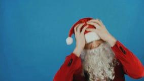 La Navidad y el Año Nuevo, hombre les gusta Papá Noel decepcionado y sacuden su cabeza, en fondo azul almacen de metraje de vídeo