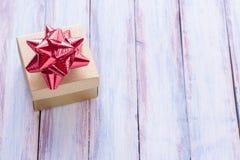 La Navidad y la Feliz Año Nuevo broncean la caja de regalo y la cinta roja con Imagenes de archivo