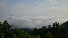 La nebbia di mattina rotola attraverso le montagne e consuma la macchina fotografica stock footage