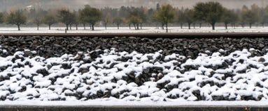 La neige blanche sur des voies ferrées et l'épaule rocheuse de remblai avec la neige ont couvert les champs et le verger d'arbre  photo stock