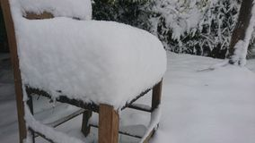 La neige a couvert la chaise dehors dans le jardin Image stock