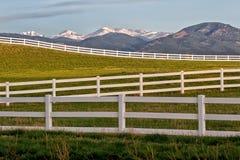 La neige a couvert des crêtes de montagne et la clôture blanche de rail fendu Images stock