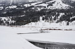 La neige a couvert des montagnes, des arbres, et la rivière Images stock