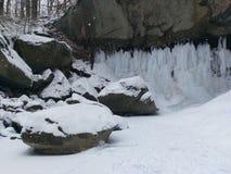 La neige a couvert des roches en bas de cascade dans le jour froid de janvier Image libre de droits