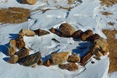 La neige a couvert l'anneau de roche du feu de camp Photographie stock libre de droits