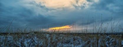 La neige a couvert l'herbe et un coucher du soleil photos stock