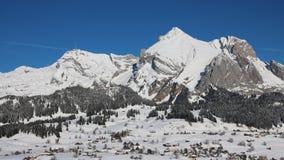 La neige a couvert la chaîne d'Alpstein et les maisons du village Wildhaus Photographie stock