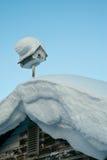 La neige a couvert la maison d'oiseau sur un toit en hiver Images stock