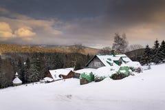 La neige a couvert la maison pendant le coucher du soleil dans un pays givré de montagnes Photos libres de droits