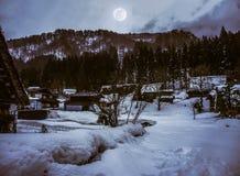 La neige a couvert la terre en hiver Ville avec le ciel nocturne et la pleine lune Images stock