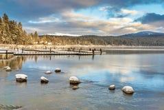 La neige a couvert le lac de montagne de roches et le Doc. de bateau photo stock
