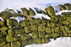 La neige a couvert le mur de pierres sèches Photo libre de droits