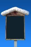 La neige a couvert le poteau indicateur en bois et le ciel bleu Photographie stock libre de droits