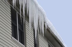 La neige a couvert le toit de longs glaçons accrochant au-dessus du Eaves-à travers photo stock