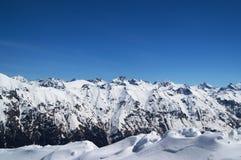 La neige a couvert les montagnes et le ciel clair bleu Photos stock