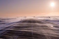 La neige d'entraînement entre à travers la route, l'obscurcissant presque pendant les vents lourds dans l'Islande du sud photographie stock libre de droits