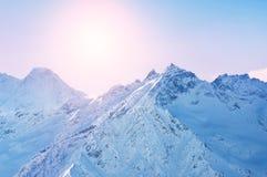 La neige d'hiver a couvert des montagnes au coucher du soleil Images stock