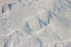 La neige de fond ondule au coucher du soleil par le vent Photographie stock libre de droits