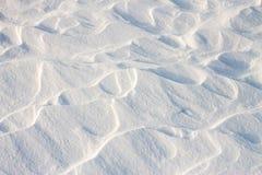 La neige de fond ondule au coucher du soleil par le vent Images libres de droits