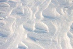 La neige de fond ondule au coucher du soleil par le vent Images stock
