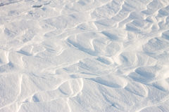 La neige de fond ondule au coucher du soleil par le vent Image libre de droits