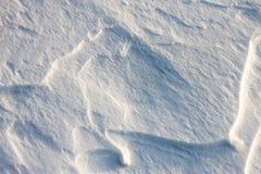 La neige de fond ondule au coucher du soleil par le vent Image stock
