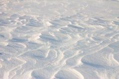 La neige de fond ondule au coucher du soleil par le vent Photos stock