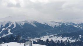 La neige de vue aérienne a couvert les montagnes et la station de sports d'hiver banque de vidéos