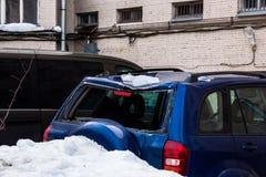 La neige des toits est tombée sur la voiture et a cassé la fenêtre arrière images stock