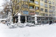 La neige empile sur des tables et des chaises dans un café Photographie stock