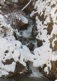 La neige et la glace couvrent partiellement une petite cascade Image libre de droits