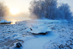 La neige et les cristaux de glace dans le lever de soleil de rivière Image libre de droits