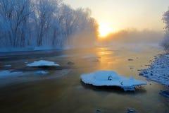 La neige et les cristaux de glace dans le lever de soleil gelé de rivière Photo stock