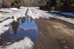 La neige résidentielle de ressort de rue se fondent Photographie stock
