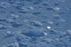 La neige s'écaille sur la glace Photographie stock libre de droits