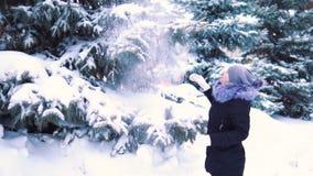 La neige tombe de l'arbre à la fille, tir au ralenti, parc couvert de neige d'hiver banque de vidéos