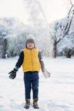 La neige tombe sur le garçon près de la forêt Photographie stock